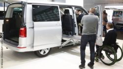 Photo: Trade fair visitors stand in front of a wheelchair-accessible vehicle at REHACARE 2018; Copyright: Messe Düsseldorf / ctillmann