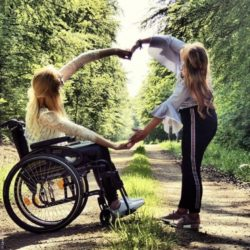 Photo: Carolin Wegner in a wheelchair and a friend forming a heart together with her arms; Copyright: Carolin_We_