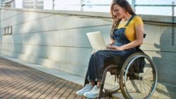 Photo: Young woman in a wheelchair typing on a laptop standing on her lap; Copyright: PantherMedia/ufabizphoto