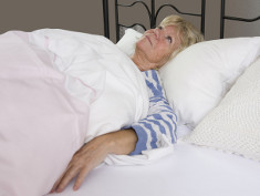 Photo: Old woman sleepless in bed