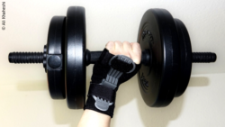 Image: a hand wearing splints is holding dumbbell; Copyright: Ali Khaheshi