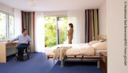 Photo: Man in wheelchair is together with his wife in an accessible hotel room; Copyright: Heidehotel Bad Bevensen@FDS Hotel gGmbH