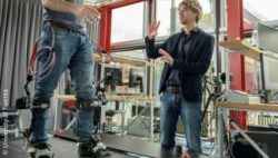 Photo: Researcher with person using an exosceleton on a treadmill; Copyright: University of Twente