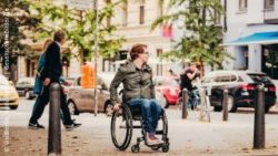 Photo: Wheelchair user standing at a street and looking to his left side; Copyright: visitBerlin, Andi Weiland | Gesellschaftsbilder.de