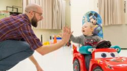 Photo: Researcher Sam Logan high-fives a child sitting in a Go Baby Go car; Copyright: Sam Logan