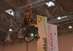 Photo: A wheelchair-user under the roof of hall 7a; Copyright: beta-web/Hofmann