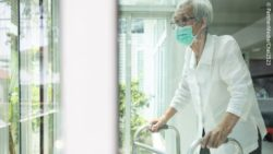 Photo: Elderly woman in a nursing home with a wheeled walker using a nose and mouth mask; Copyright: PantherMedia/Chai2523