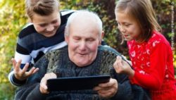 Photo: Elderly man using a tablet and gets some help from two children; Copyright: panthermedia.net/Barabasa