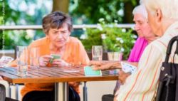 Photo: Seniors playing board game on the terrace of a nursing home; Copyright: panthermedia.net/Arne Trautmann