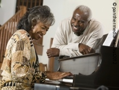 Photo: Elderly woman playing the piano, smiling man