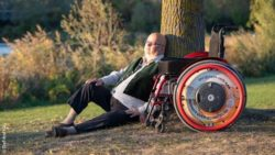 Photo: Richard J. Schaefer sitting under a tree, next to him is his wheelchair; Copyright: DieFotoFrau