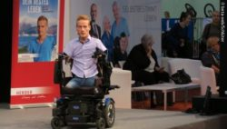 Photo: Janis McDavid on the stage at REHACARE; Copyright: beta-web/Schlüter