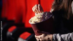 Photo: Young woman eating popcorn in the cinema; Copyright: panthermedia.net/stokkete