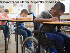 Photo: Three students in class, one of them in a wheelchair