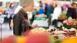 Photo: Woman buying vegetables at a local food market; Copyright: panthermedia.net/matej kastelic