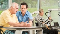 Photo: A physiotherapist sits together with an elderly patient and performs exercises, in the background a patient sits on a robotic-assisted therapy device; Copyright: Hocoma, Switzerland