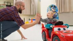 Photo: A child using a Go Baby Go car and giving high five to a researcher; Copyright: Oregon State University