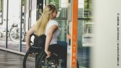Photo: Woman in a wheelchair drives through an accessible entrance of a huge building; Copyright: visitBerlin, Andi Weiland | Gesellschaftsbilder.de