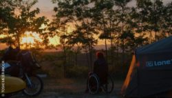 Photo: Woman in a wheelchair standing between a tent and a motorcycle watching the sunset; Copyright: TOSHI MEIER-BROOK