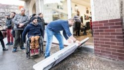 Photo: A shop owner who allows a wheelchair user access to his shop by means of a mobile ramp; Copyright: Jörg Farys | AG Urban