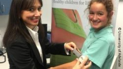 Photo: Researcher is fitting a wearable sensing device to a girl
