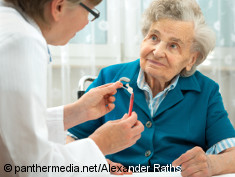 Photo: Woman talks to elderly woman holding a hearing-aid