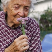Photo: Old woman smelling a flower