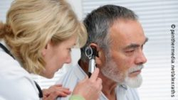 Photo: Physician checking the ear of an elderly man