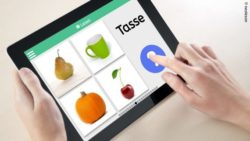 Photo: A hand that assigns the correct image to a displayed term in the neolexon app on the tablet; Copyright: neolexon