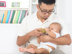 Photo: A man feeding an infant with a bottle