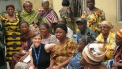 Photo: Female researcher from Europe sitting between African women; Copyright: Institute of Tropical Medicine Antwerp