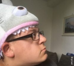 Image: Young man with glasses wears a shark-shaped hat; Copyright: private