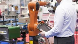 Photo: A man programming and operating a robotic arm; Copyright: panthermedia.net/Mihajlo Maricic