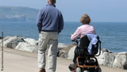 Photo: Man and his wife who uses a power wheelchair on a beach promenade; Copyright: panthermedia.net/ronfromyork