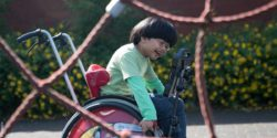 Image: A dark-haired boy in a red wheelchair travels over the playground; Copyright: REHAVISTA