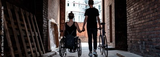 Photo: Young woman in a wheelchair holding hands with her boyfriend who walks next to her with his bike in the other hand; Copyright: Andi Weiland | Gesellschaftsbilder.de