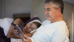 Photo: Middle aged couple laying in bed. The Man using his tablet computer while his wife is sleeping; Copyright: panthermedia.net/Monkeybusiness Images