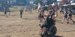 Photo: Andrea Schütt posing in her wheelchair on the grounds of the Wacken Open Air; Copyright: private