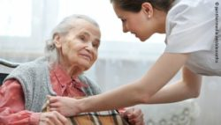 Photo: Elderly woman smiling at a nurse; Copyright: panthermedia.net/alexraths