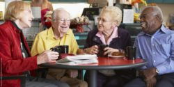 Photo: Four happy elderly people sitting in a cafe and talking; Copyright: panthermedia.net/Monkeybusiness Images
