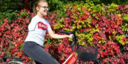 Photo: Heidi Ulm riding a bike in front of a colorful hedge; Copyright: private