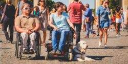 Photo: Man and woman in a wheelchair stand in front of the Brandenburger Tor in Berlin together with their assistance dog; Copyright: visitBerlin, Andi Weiland | Gesellschaftsbilder.de