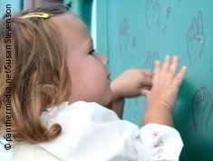 Photo: Girl looking at sign language alphabet