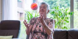 Photo: An elderly woman catches ichó. The ball starts to glow in red-orange colors.; Copyright: ichó systems - icho-systems.de