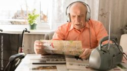 Photo: Elderly man sitting at the table and listening to music from radio with headset while reading a newspaper; Copyright: panthermedia.net/Vaicheslav