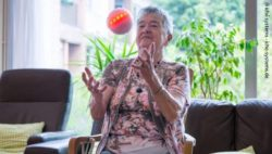 Photo: An elderly lady catches ichó. The ball shines red-orange; Copyright: ichó systems - icho-systems.de