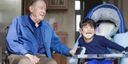 Photo: Elderly man in a wheelchair and a disabled boy laugh together; Copyright: panthermedia.net/jarenwicklund