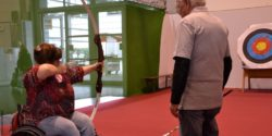 Image: A female visitor is doing archery in the Sports Center at REHACARE 2017; Copyright: beta-web/Hofmann