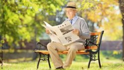 Image: An older man with a hat is reading a newspaper on a bench in a park; Copyright: PantherMedia/ljsphotography