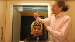 Photo: A researcher applies contact gel on the test person; Copyright: Michael Veit